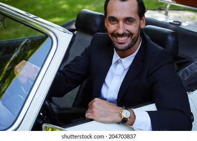 Rich confident handsome businessman sitting in the cabriolet classic car and smiling at camera, lifestyle and successful business concept