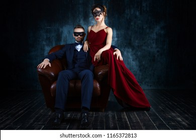 Rich couple man male woman female in love sitting in leather sofa in expensive suit and red evening dress and black carnaval mask. Sex, tempts, harassment, sexism, seduction issues