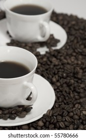 A rich cup of hot coffee, with fresh roasted beans