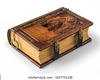 """Rich decorated handmade leather bound journal named """"Anatomia humani corporis"""" laying on the table"""