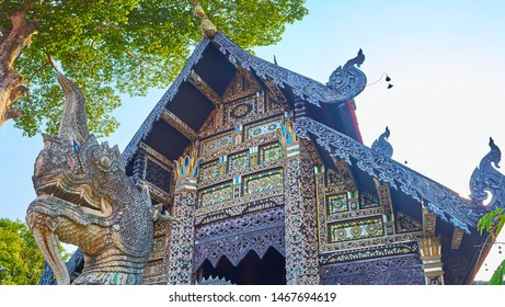 Rich decorations of Bhuridatto Viharn - Naga serpent in front of hall with carved pyathat roof, bargeboards with chofa Nagas, ornate panels of teak and mirror, Wat Chedi Luang, Chiang Mai, Thailand
