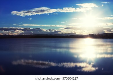 Rich, deep colors featured in this mirrored image of clouds reflected in a calm lake