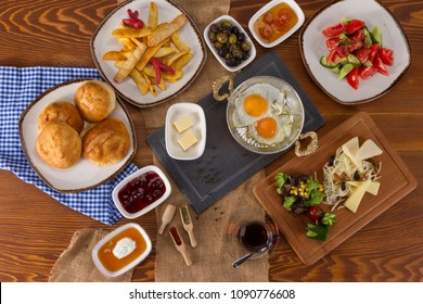 Rich Delicious Turkish and Arabic Traditional Breakfast serving on wood table ingredients with Egg, Butter, Fried Potatoes, Olives, Fresh Vegetables, Various Cheese, Bread Pisi, Patty and Black Tea.