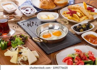 Rich Delicious Turkish and Arabic Traditional Breakfast serving on wood table ingredients with Egg, Ham, Butter, Fried Plate, Olives, Fresh Vegetables, Various Cheese, Bread Pisi, Borek and Black Tea.