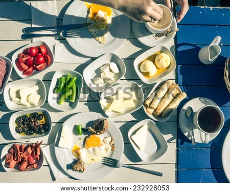 Rich and delicious Turkish breakfast on white wooden table. Toned image