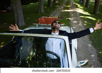 Rich elegance man with arms raised and feeling of freedom sitting behind the wheel of cabriolet classic luxury car, lifestyle and successful business concept