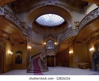 Rich entrance hall in the Lviv ancient casino with stained-glass window, twisted staircase and laced rails.