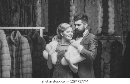 Rich fashion concept. Man and girl with happy face choose furry coats on clothes rack background. Couple in love tries expensive sable overcoats. Shop assistant with beard and woman select furry coat
