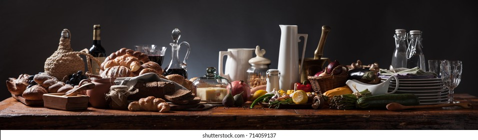 Rich food table, medieval style, panorama on rustic wood table and dark background.