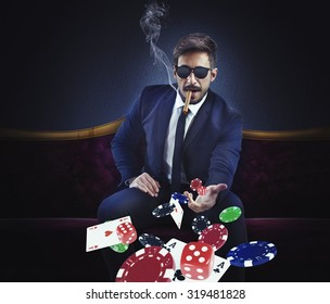 Rich gambler throws cards dice and chips