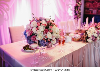 Rich garland of white roses and pink hydrangeas lies on the pink dinner table