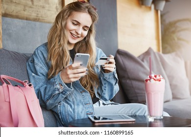Rich girl paying for everyone, celebrating promotion at work, sitting in fancy cafe wearing stylish outfit, holding smartphone and credit card, talking casually while making payment via internet app