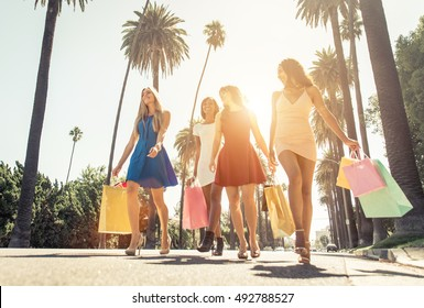 Rich girls made shopping in Beverly hills, california. Happy smiling women with bags walking on the street