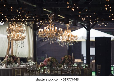 Rich golden chandeliers hang above a wooden ceiling over restaurant's tables