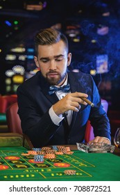 Rich handsome man smoking cigar and playing roulette in the casino
