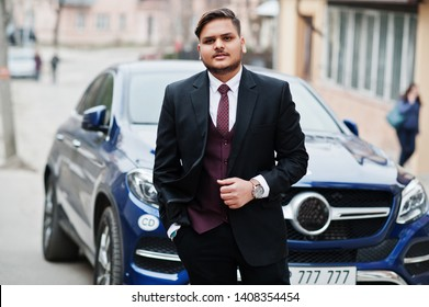Rich indian businessman in formal wear standing against business suv car.