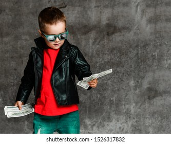 Rich kid boy millionaire in sunglasses, leather jacket, red t-shirt and stylish torn jeans is looking at bundles of dollars cash in his hands on concrete background with copy space