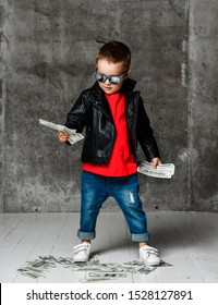 Rich kid boy in sunglasses, leather jacket, red t-shirt and blue jeans is looking at bundle of cash in his hands dropping money on the floor on concrete wall background