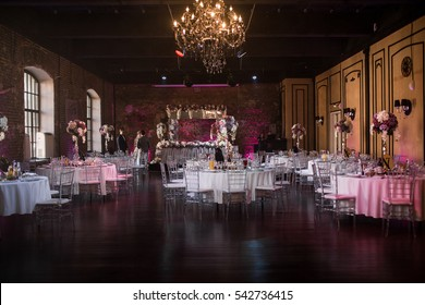 Rich large hall with round white tables prepared for wedding dinner