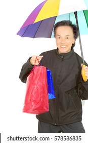 rich looking chinese shopping man with beautiful white teeth smiling holding umbrella left handed and bags right hand. white background