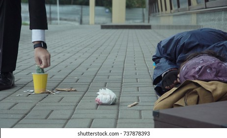 Rich man passerby giving money to sleeping homeless man.