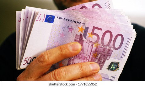 a rich man shows 10,000 euros in many 500 euro notes