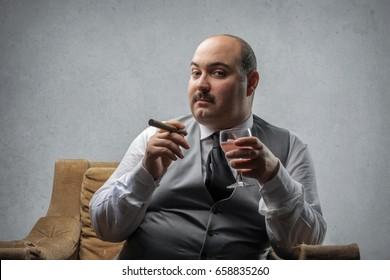 Rich man sitting in an armchair smoking a cigar
