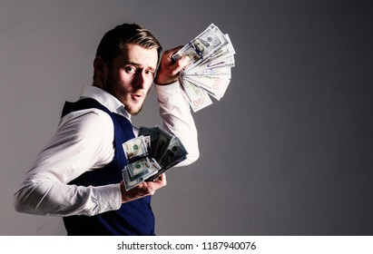 Rich man, successful entrepreneur get cash, banknotes, currency, dollars. Boasting concept. Man in waistcoat, businessman, entrepreneur holding lot of money in both hands, grey background.