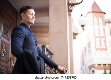 A rich man in a suit on the terrace of his luxury home.