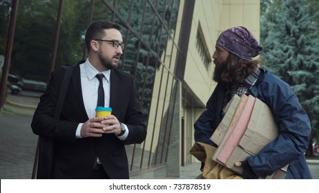 Rich man weared in suit with coffee walking on street and talking to homeless person.