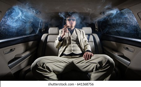A rich man in a white suit and a cigar in the car, a limousine