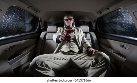 A rich man in a white suit and a cigar with a glass of wine in the car, a limousine