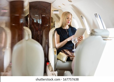 Rich mid adult woman using tablet computer in private jet