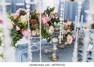 Rich pastel bouquets decorate dinner table served in blue colors