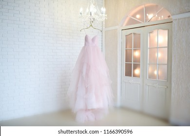 Rich pink wedding dress hangs on a chandelier in a white room