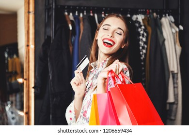 Rich pretty brunette woman laughing with credit card and colored shopping bags in fashion mall after the great shopping, concept of consumerism, Black Friday, sale, rich life
