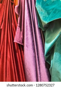 Rich red, purple and green bolts of fabric are draped from a rack in a cloth store in the souk of Marrakesh in Morocco.