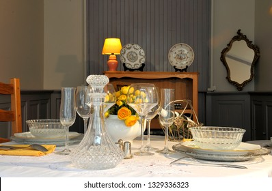 Rich set table on old fashioned dining room table with wine and flowers