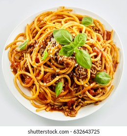 Rich spicy Italian spaghetti Bolognaise with parmesan cheese and a fresh green basil leaves viewed from overhead on a white plate in square format