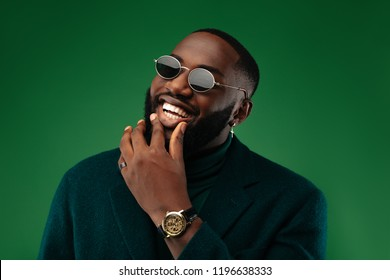 Rich and stylish. African American guy in green jacket and sun glasses is looking at camera and smiling, on a green background