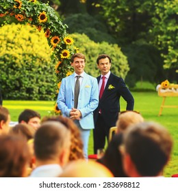 rich stylish groom with bestman waiting bride near the arch of sunflowers