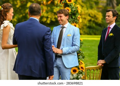 rich stylish groom and bride  with bestman near the arch of sunflowers