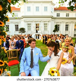 rich stylish groom and bride  kissing hand near the arch of sunflowers wedding ceremony