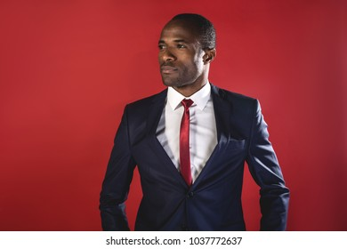 Rich and success. Portrait of elegant smart young african businessman in suit is standing and looking aside confidently. Isolated background