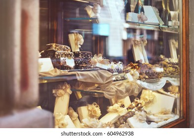 Rich variety of chocolates, candies and biscuits with a gift box in display window of italian pastry shop at the street of Florence city