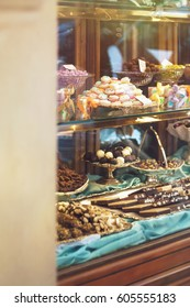Rich variety of chocolates and candies in display window of italian pastry shop in the street of Florence at sunny day