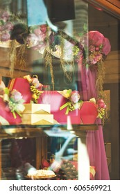 Rich variety of floral decorations and gift boxes with chocolate and candies in display window of typical italian pastry shop at sunny day at the street of Florence