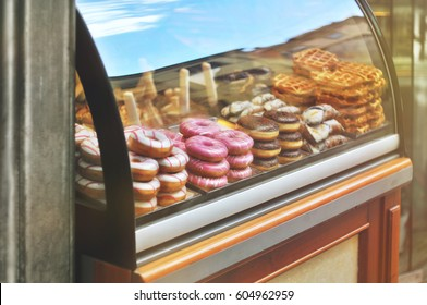 Rich variety of italian cookies, donuts, wafer in showcase of typical pastry shop in the street of Florence at a sunny day with a sky reflection on display window