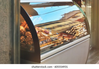 Rich variety of italian cookies, donuts, wafer in showcase of typical pastry shop in the street of Florence city at a sunny day with a sky reflection on display window