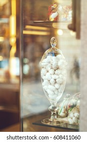 Rich variety of white chocolates, candies in glass jars in display window of typical italian pastry shop in the street of Florence with light reflection on window